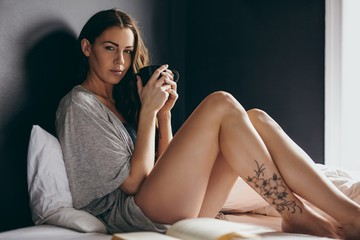 Beautiful young woman on bed with a cup of coffee