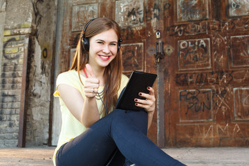 Young woman with a tablet and headphones holding thumbs up
