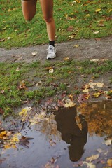 Reflection of young woman in a puddle of water in park