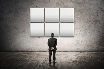 businessman watching a empty frames on the wall