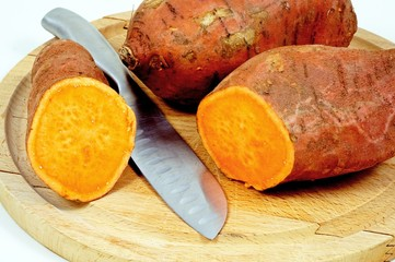 Raw sweet potatoes and a knife © Arena Photo UK