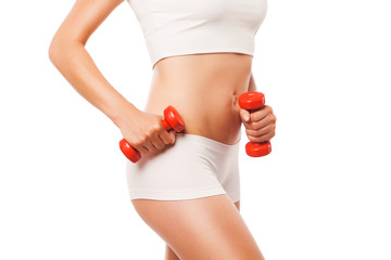Slim tanned woman's body with red dumbbells on a white