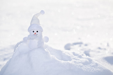 Little white snowman near snowbank.