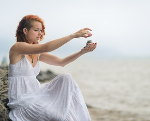 Redhead woman holding zen stones in hand.