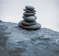 Stack of zen stones on rock in the fog. Blue toned image.