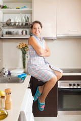 woman sitting on table at kitchen