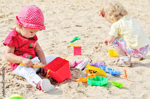 babies playing toys in sand