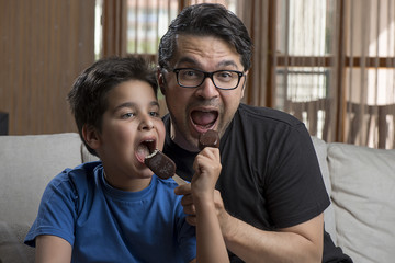 Father and son enjoying ice cream covered with chocolate