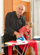 man holding  daughter and ironing