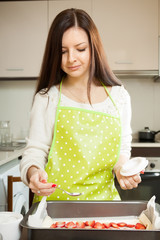 Girl in  kitchen preparing cake