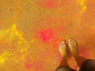 Feet on the coloured ground. Festival if colours.