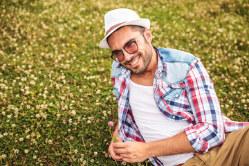 casual man picking a flower from a field and smiles