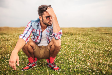crouched casual man in a grass field thinking