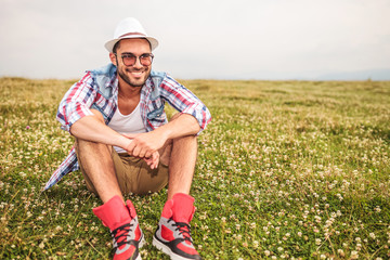 smiling young casual man sitting in a field