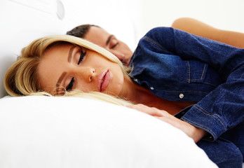 Portrait of couple sleeping on the bed