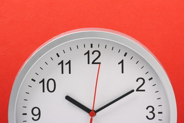 Wall clock in half profile against a bright red paper background