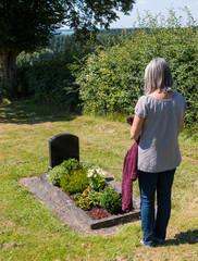 Seniorin trauert an einem Grab