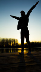 Silhouette of young woman at sunset on lake pretending to fly