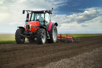 Close-up of agriculture red tractor cultivating field
