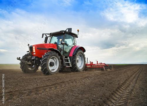 Leinwanddruck Bild Farmer in tractor preparing land for sowing