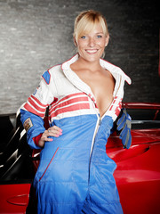 Sexy woman with racing suit in a garage