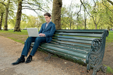 Businessman with a laptop sitting in a park