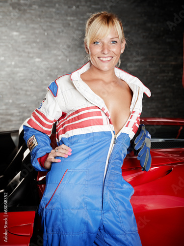 canvas print picture Sexy woman with racing suit in a garage