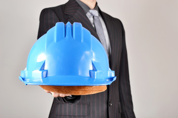 Businessman showing a helmet