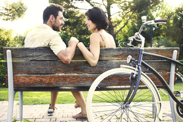 Couple in love sitted togheter on a bench with bikes