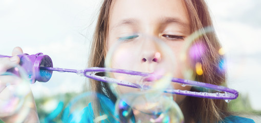 Portrait of girl blowing soap bubbles