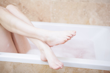 Woman's legs hanging over the edge of a bath tube.
