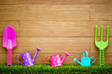 colorful gardening tools on wood and grass background
