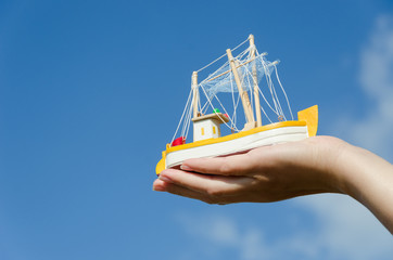 wooden ship toy on palm on blue sky background