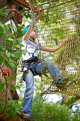 Girl is climbing on net of obstacle course
