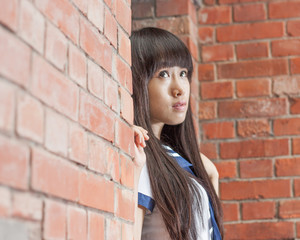 Asian schoolgirl outside brick building