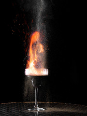 Flaming cocktail with gray pepper