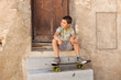 Young boy resting on steps with skateboard