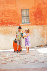 Young couple with suitcase in exterior