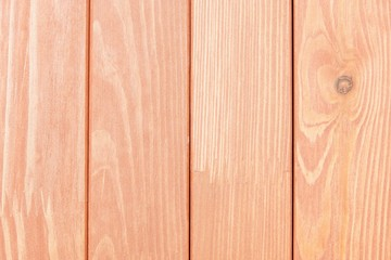 the textured wooden surface of pale red color