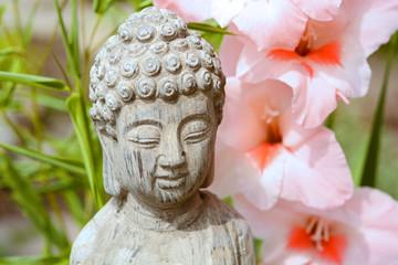 Boeddha in  bamboe tuin met bloemen
