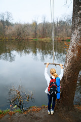 Woman hiker with bungee in the hands near autumn river