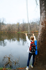 Woman traveler with bungee in the hands near autumn river