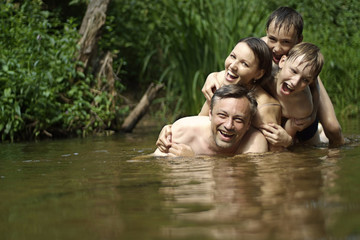 Beautiful family swims in the river