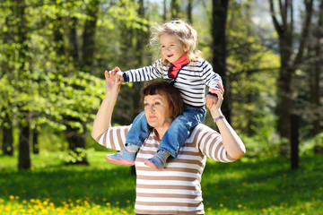 Grandmother and granddaughter playing on the meadow of ye