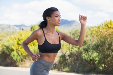 Fit woman running along the open road