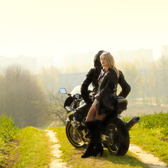 blonde with a biker posing near a sports bike.