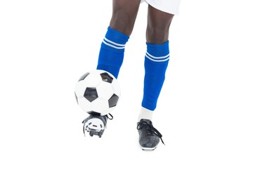 Football player in blue socks kicking ball