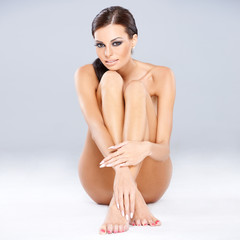 Young sexy brunette sitting while isolated on gray
