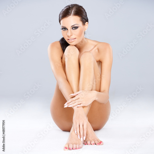 canvas print picture Young sexy brunette sitting while isolated on gray