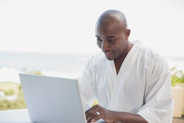 Handsome man in bathrobe using laptop at breakfast outside